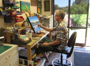 Bernard Carroll painting at his desk in the studio.
